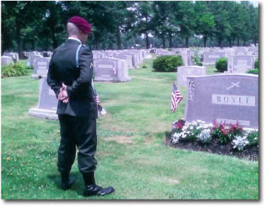 Pvt. Robert Dembowski Jr. Stands in uniform before his grandfather\'s grave. Ironically, he was to be buried mere yards from that spot 8 months later.